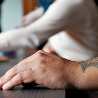Arm with tatoos resting on a table with other people in background