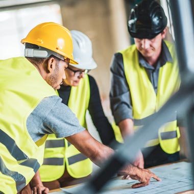 Building site workers around table looking at plans