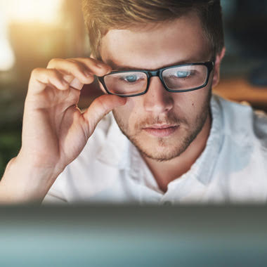 Man looking at computer screen while adjusting his glasses