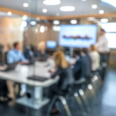 Blurred image of a team around a board table looking at a screen a one end