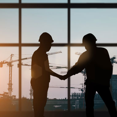 Two construction workers shaking hands with cranes in the distance